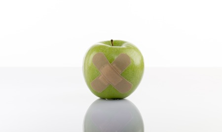 superficial: A Green apple with a band-aid on white background