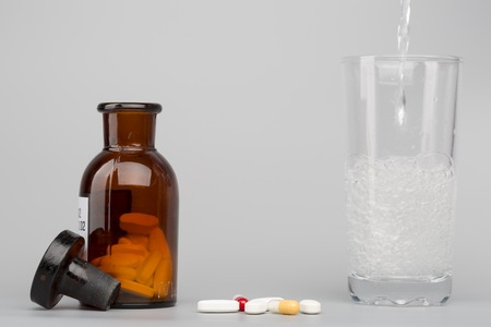 fizzy tablet: Various  colored pills,medical bottle an glass of water