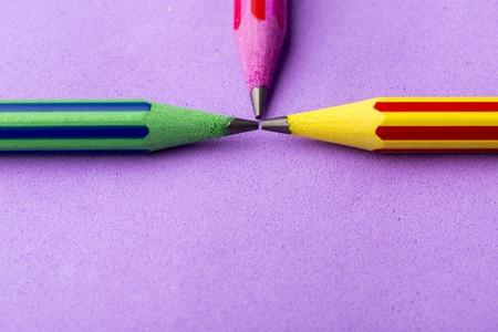 schoolroom: Three school colorful pencils on purple background Stock Photo
