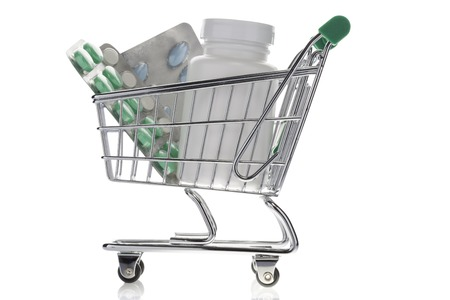 shopping cart isolated: Pill bottle and pills in shopping cart isolated on white. Concept. online pharmacy