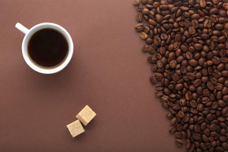 fondo cafe: Taza de caf�, el az�car moreno y frijoles en un fondo marr�n. Sobre la opini�n