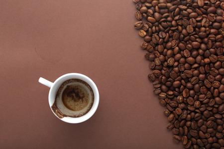 borracho: Taza de café bebido en el fondo marrón con vista beans.Top café