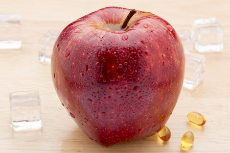 Fish oil pills and fresh red apple on wooden background