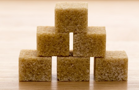sugar cubes: Brown cane sugar cubes on wooden background.Macro closeup