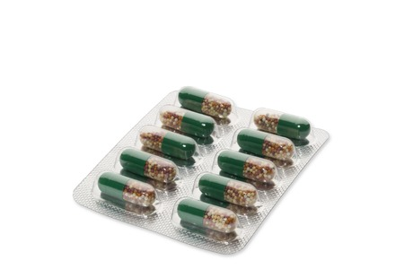 blister package: Green pills in a blister package on white background