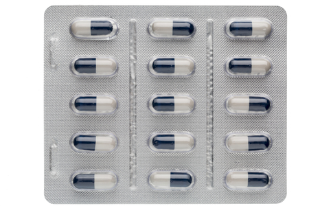 blister package: Closeup dark blue and white capsules in medication blister package on white background