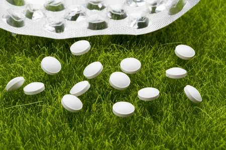 pilule: Pastillas antibi�ticas blancas y blister vac�os esparcidos sobre la hierba verde Foto de archivo