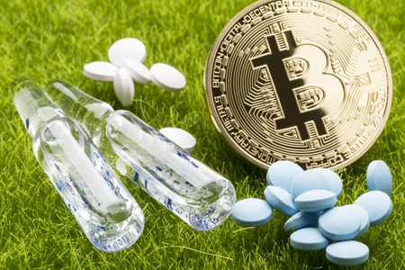 ampules: Different pills and ampules with bitcoin coin on the green grass background - healthcare cost concept