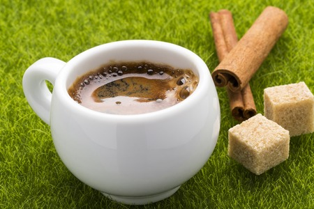 cofe: Coffee hot cup and cinnamon sticks with cubes brown cane sugar on the green grass. Stock Photo