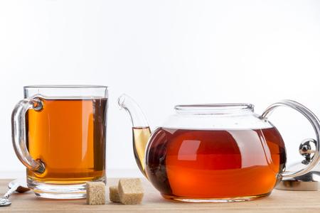Transparent teapot and cup of black tea