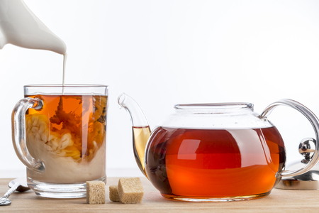dissolve: Dissolve milk in a cup of black tea. Transparent teapot and cup with three cubes of brown sugar on white background