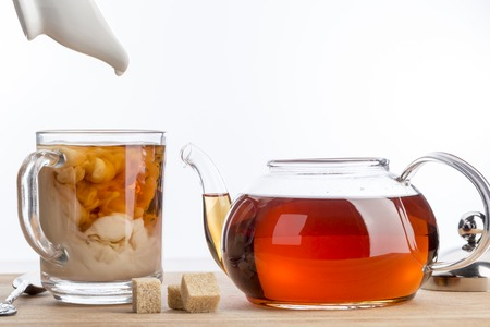 dissolve: Dissolve milk in a cup of black tea. Transparent teapot and cup with three cubes of brown sugar Stock Photo