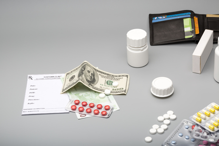 herbal background: Blank prescription,blister pack,scattered pills, open wallet and hundred dollar and euro banknotes