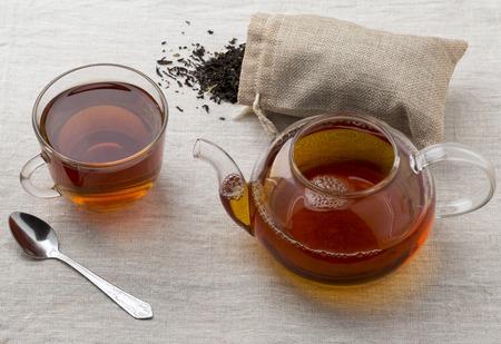 Schwarzer Tee in einer Glasschalen- und Glasteekanne frisch gebraut auf einer Serviette von einem Rausschmiß