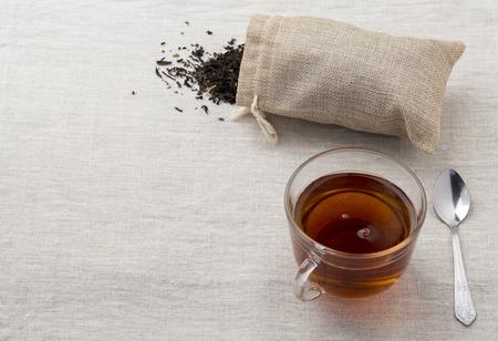 Schwarzer Tee in einer Tasse Glas und Teekanne aus Glas frisch auf einer Serviette aus einem Rausschmiß gebraut