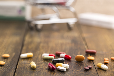 pilule: Colorful pills,capsules and pill box on dark wooden background Foto de archivo