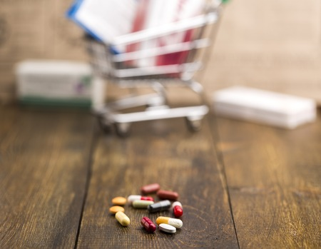 pill box: Colorful pills,capsules,pill box and shopping cart on dark wooden background Stock Photo