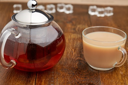 teacup: Set of glass teapot and tecup of black tea with milk on wooden table Stock Photo