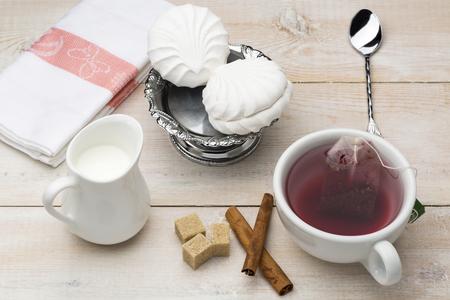 red tea: Set of cup red tea and dessert on bright wooden table Stock Photo