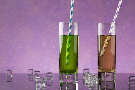 collins: Set from two a Collins glass with soda and colored straws. Decorated melted ice cubes. Stock Photo