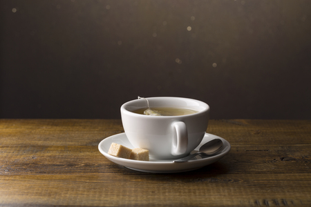 tea bag: Tea cup with tea bag on saucer.Wooden background