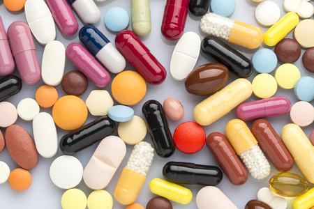 pilule: Pharmaceutical background of multi-colored tablets and capsules scattered on the surface