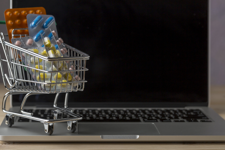 retail therapy: Shopping cart filled with blister on top open notebook