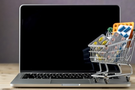 emergency cart: Mini shopping cart with pill blister pack on open laptop.Concept forn online store