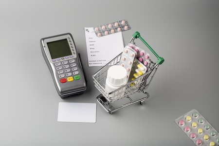emergency cart: Pos terminal and shopping cart full of various pills