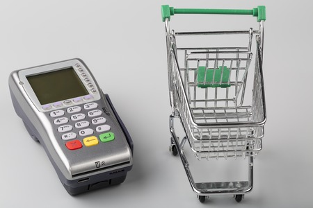 empty shopping cart: Credit card machine with empty shopping cart on gray background