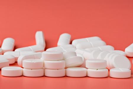 sobredosis: Montón de píldoras redondas blancas sobre fondo de color rosa Foto de archivo