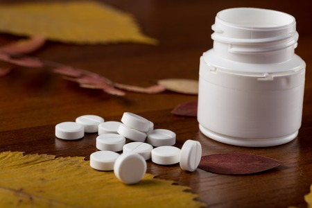 pill bottle: Heap of round white pills and pill bottle on yellow leaves