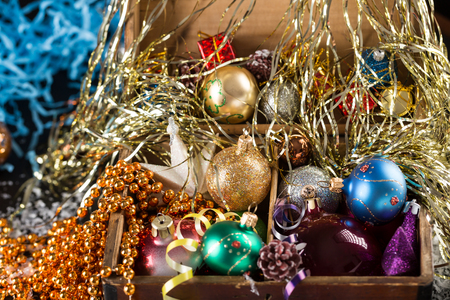 december 25: Colorful Christmas balls in a old wooden box on shiny background