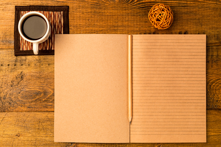 hoja en blanco: Lugar de trabajo. libreta de artesanía abierta con lápiz. Taza de café recién hecho Foto de archivo