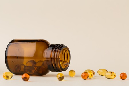 Bottle of pills from the brown glass and fish oil
