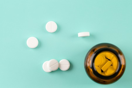 Brown glass pills bottle and round pills Stock Photo