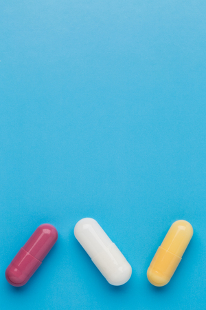 Three multi colored pills on blue background