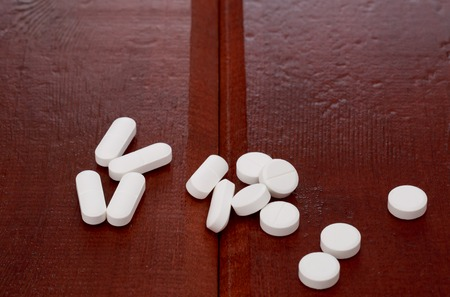 scattering: Various white pills on wooden table
