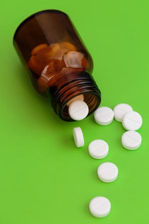 Glass bottle and pile of white pills on green background