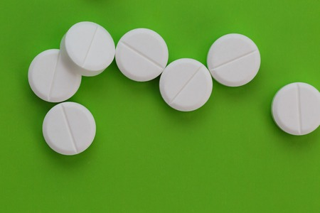 Pile of white pills on green background