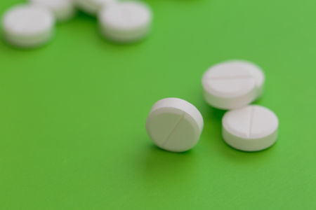 Heap of white pills on green background Stock Photo