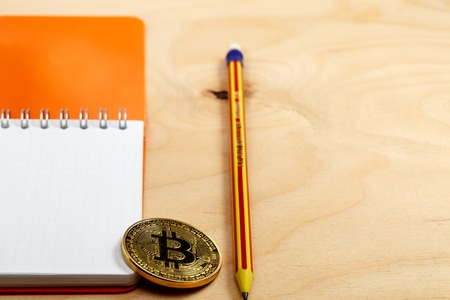 The cryptocurrency bitcoin coin on open notepad. Stock Photo