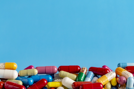 Heap of colorful drugs and pills on color background Stock Photo