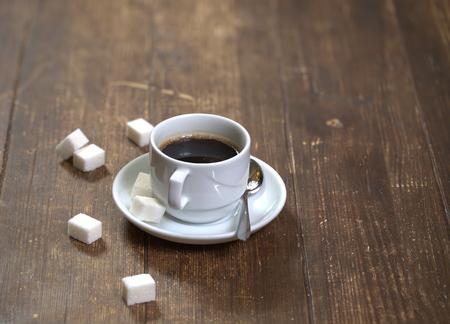 Tasse à café en céramique blanche, cuillère à café brillante et morceaux de sucre blanc sur une vieille table en bois Banque d'images