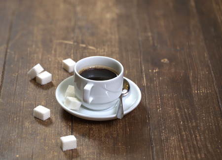 White ceramic coffee cup, shiny coffee spoon and pieces of white sugar on an old wooden table