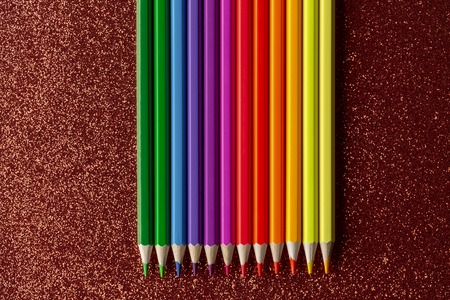 Colored pencils on glitter red background 版權商用圖片