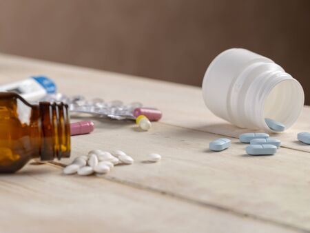 Glass and plastic bottles of medicine. Blue tablets and colored medical capsules Stock Photo