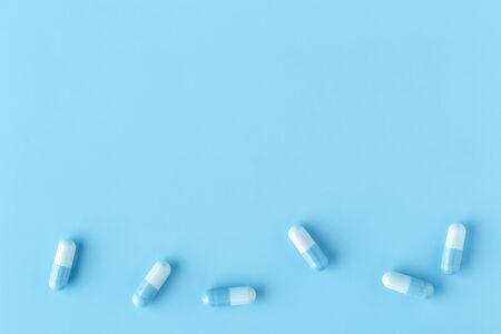 Various white-blue medication capsules. Blue background with copy space