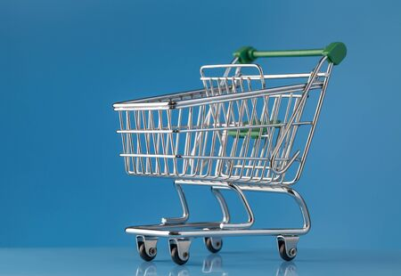 A shiny new shopping cart on a blue background. Close-up Stock Photo