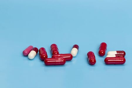 Red-white medicinal capsules on blue background
